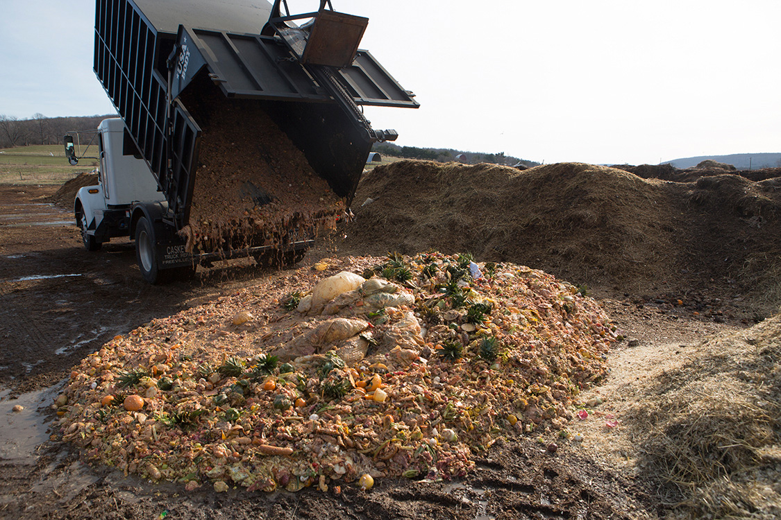Truck dumping organic material onto a large compost pile
