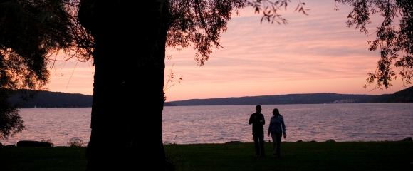 Students enjoy the view of Cayuga Lake at sunset in Stewart Park