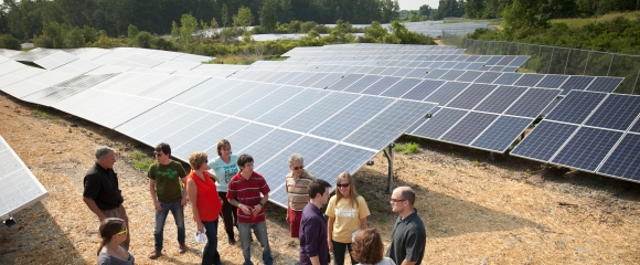 Group listens to lecture next to a solar array owned by Cornell