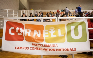 Students hold a banner for Recyclemania while at a basketball game