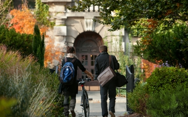 Two students wearing jackets walk a bike through campus greenery in the Fall