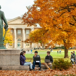 Students study next to Ezra cornell statue