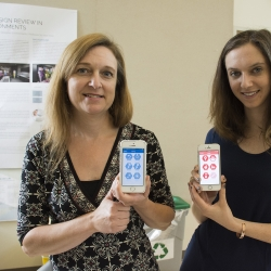 Two students hold up cellphones showing the HumbleBee app interface
