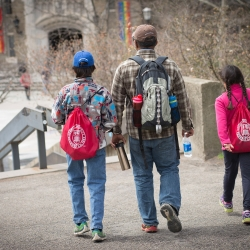 A parent with two young children wearing Cornell backpacks