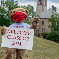 Big red bear welcomes students to campus during COVID, wearing a mask