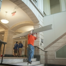 An employee carrying a beam through Warren Hall