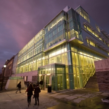 The glass facade of the Physical Sciences Building lit up in the evening.