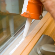 caulking a window frame to prevent air leakage