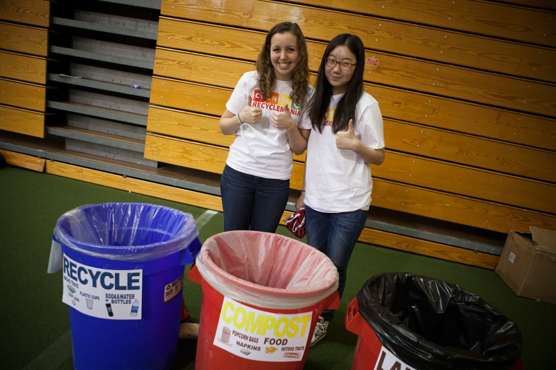 students managing recycling and compost bins at a campus event
