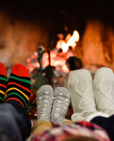 Two adults and one child's socked feet in front of a fire